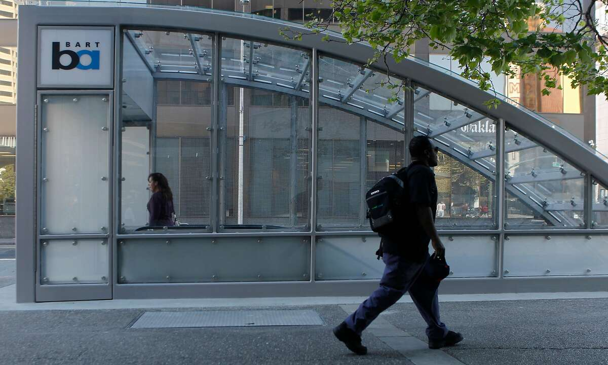 Commuters walk past the new canopy over the 19th Street Bart Station entrance at 20th and Broadway streets in Oakland, Calif. is opened to the public Friday, March 6, 2015.