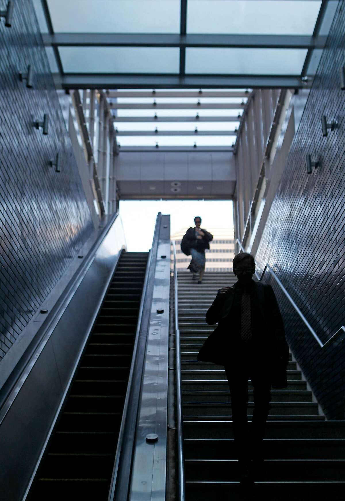 Commuters enter 19th Street BART through the new canopy over the entrance at 20th and Broadway streets in Oakland, Calif. is opened to the public Friday, March 6, 2015.