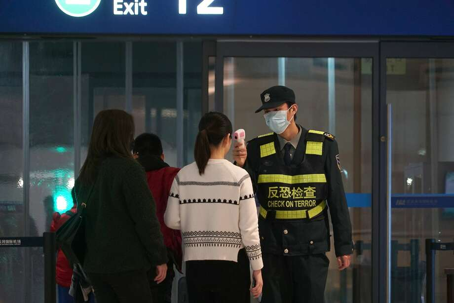An airport staff member uses a temperature gun to check people leaving Wuhan Tianhe International Airport in Wuhan, China, Tuesday, Jan. 21, 2020. Heightened precautions were being taken in China and elsewhere Tuesday as governments strove to control the outbreak of a novel coronavirus that threatens to grow during the Lunar New Year travel rush. Photo: Dake Kang, Associated Press