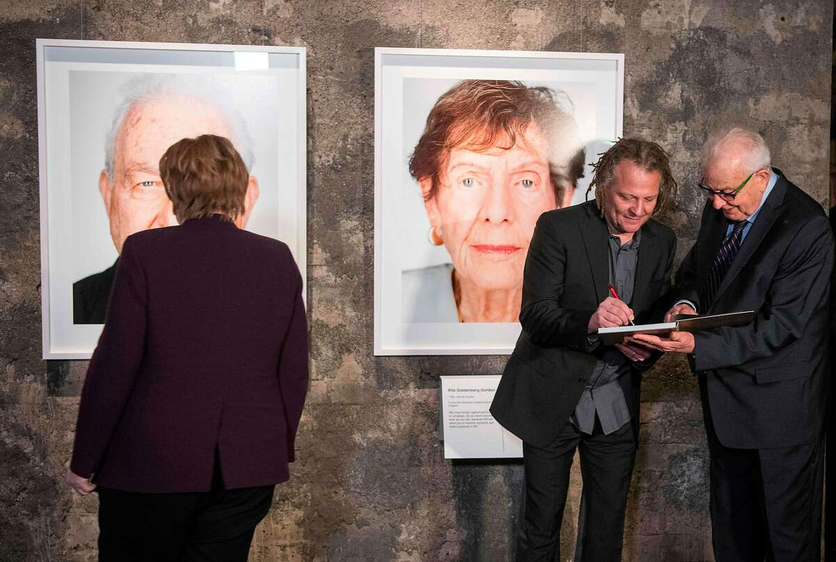 German Chancellor Angela Merkel (L) stands in front of a portrait of an Holocaust survivor as German photographer Martin Schoeller (C) signs an autogram to Holocaust survivor Naftali Furst during the opening of an exhibition at the UNESCO World heritage Kokerei Zollverein in Essen, on January 21, 2020. - The award-winning German portrait photographer Schoeller featured 75 Holocaust survivors in a commemorative photo project that Israels Yad Vashem Holocaust memorial produced last year in Jerusalem to mark 75 years since the liberation of Auschwitz.