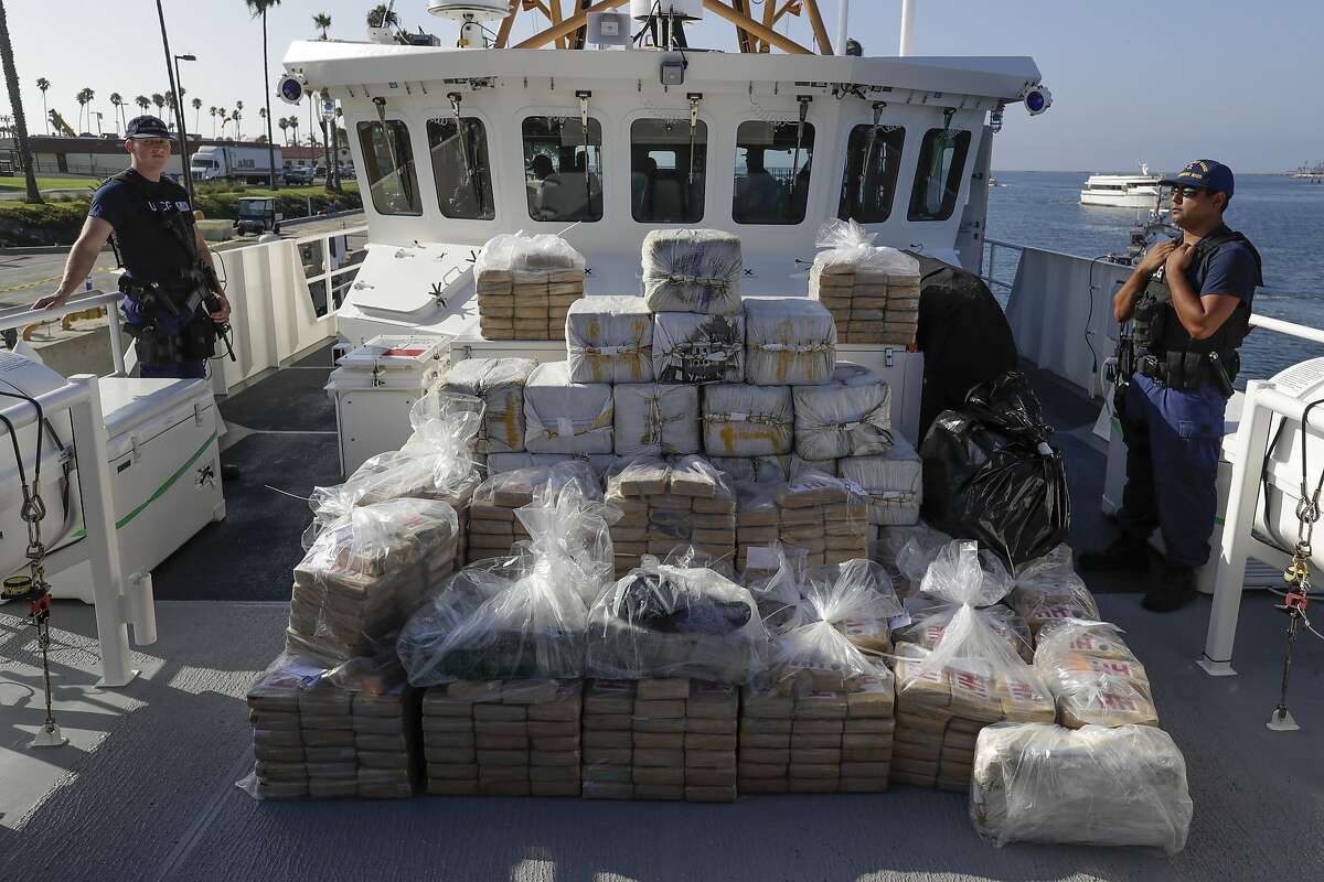 In this Aug. 29, 2019, file photo, members of the Coast Guard stand near seized cocaine in Los Angeles. The nation's drug addiction crisis has been morphing in a deadly new direction: more Americans struggling with meth and cocaine. Now the government will allow states to use federal money earmarked of the opioid crisis to help people addicted to those drugs as well. The change to a $1.5 billion opioid grants program was buried in a massive spending bill that Congress passed late in 2019.