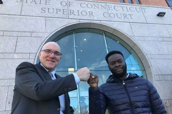 Criminal Defense Attorney Allan Friedman and Emmanuel Mong fist bump in celebration of larceny and conspiracy charges being thrown out against Mong at the Stamford courthouse Tuesday morning.