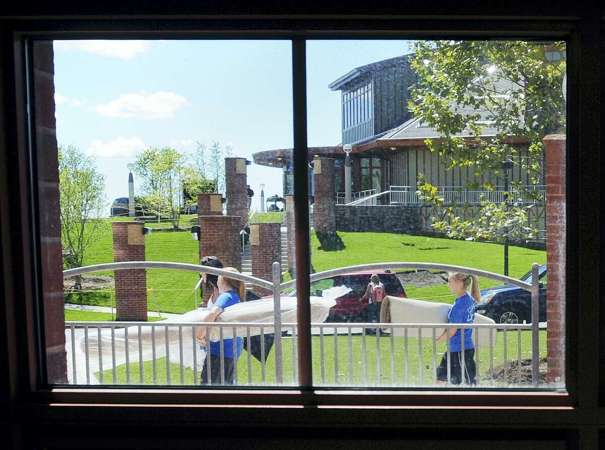 Students walk past the Rocky Top Student Center as they move into the Crescent residence hall on Quinnipiac University's York Hill campus.