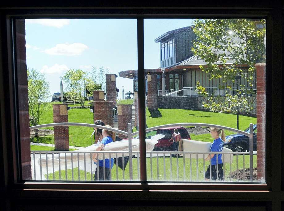 Students walk past the Rocky Top Student Center as they move into the Crescent residence hall on  Quinnipiac University's York Hill campus. Photo: AP / New Haven Register