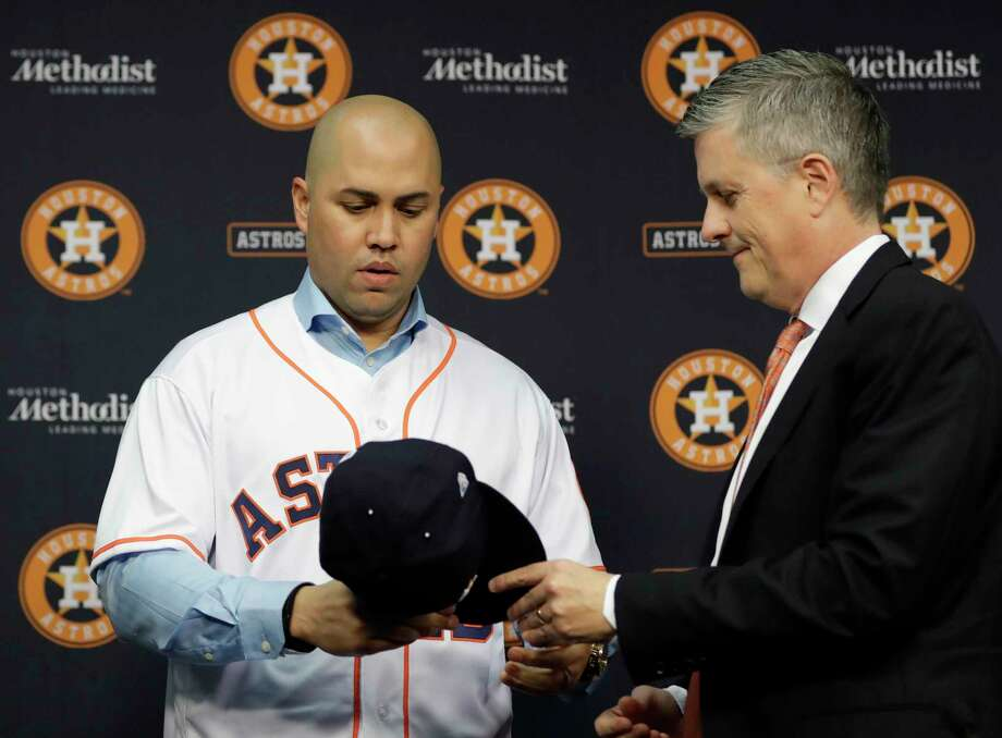 In this Dec. 5, 2016, file photo, Houston Astros general manager Jeff Luhnow, right, hands outfielder Carlos Beltran a cap during a news conference to announce Beltran's signing a one-year contract with the team, in Houston. Beltran is out as manager of the New York Mets, the team announced last week, in connection with sign-stealing while on the Astros. Photo: Associated Press / Copyright 2016 The Associated Press. All rights reserved.