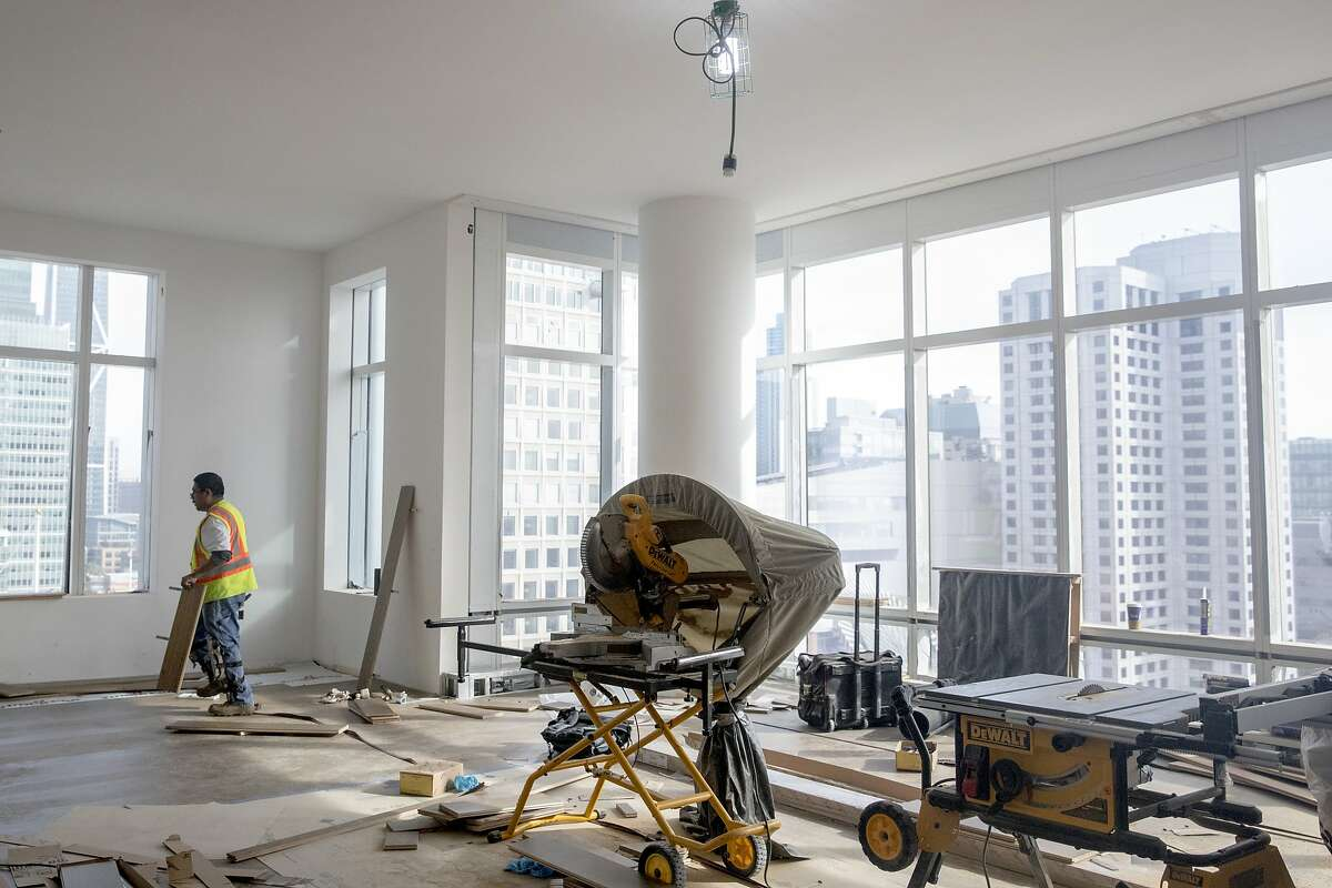 Crews work to install hardwood floors inside an apartment under construction at the Four Seasons Private Residence 706 Mission in San Francisco, Calif. Friday, December 20, 2019.