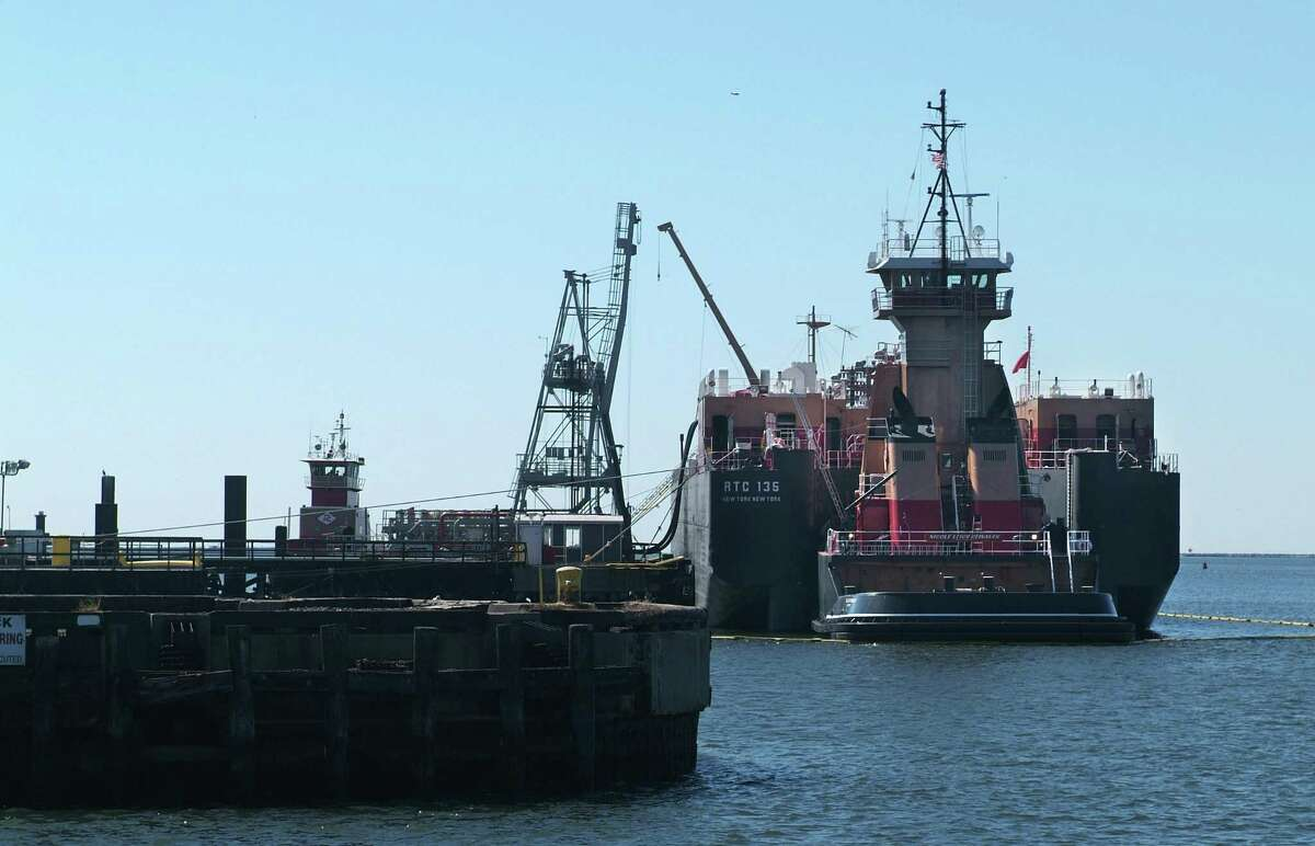 An oil barge unloads fuel along terminal row in New Haven.