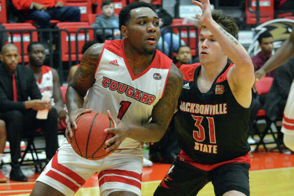 SIUE sophomore Kenyon Duling, left, drives to the basket during Saturday's Ohio Valley Conference game against Jacksonville State at First Community Arena at the Vadalabene Center.