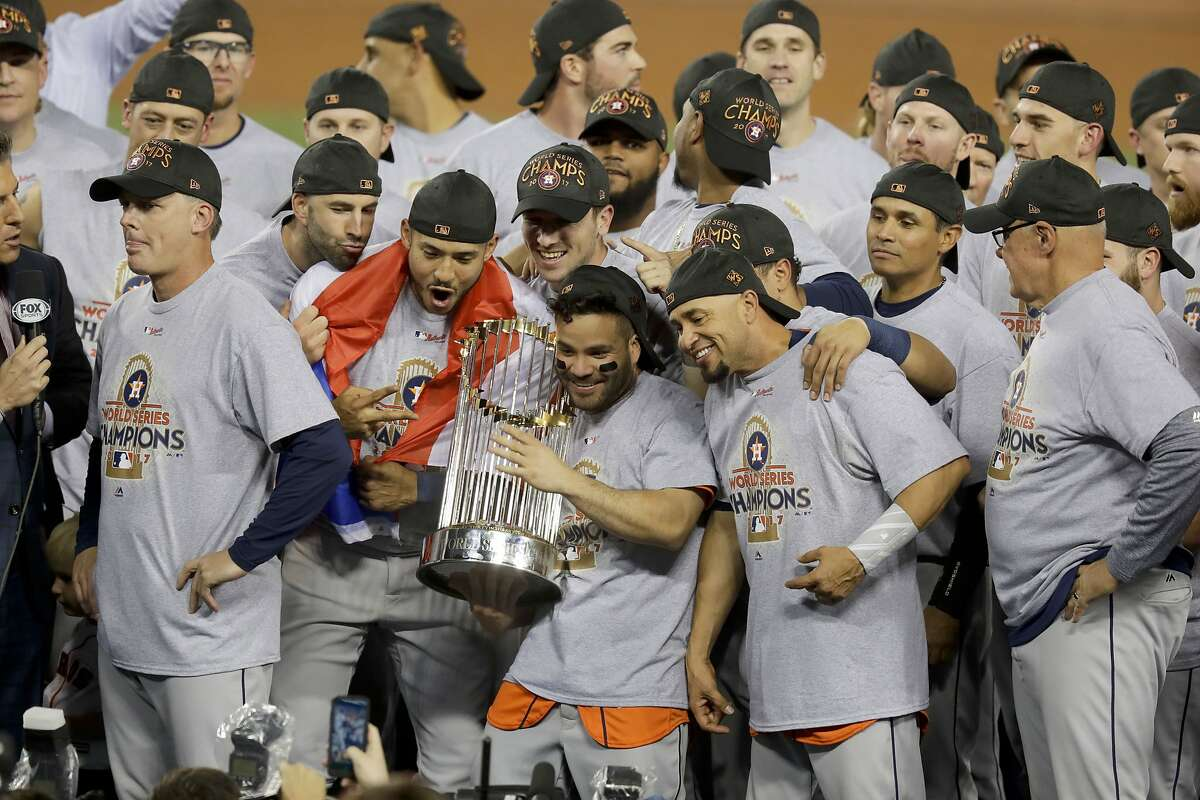 FILE - In this Nov. 1, 2017 file photo, the Houston Astros celebrate with the trophy after their win against the Los Angeles Dodgers in Game 7 of baseball's World Series in Los Angeles. The Los Angeles City Council wants Major League Baseball to strip the Houston Astros and Boston Red Sox of their World Series titles and award the trophies to the Dodgers. The resolution was introduced Tuesday, Jan. 21, 2020, after it was revealed that the Astros used a system by then-coach Alex Cora in 2017 to tip off batters on what pitch was to be thrown. (AP Photo/Alex Gallardo, File)