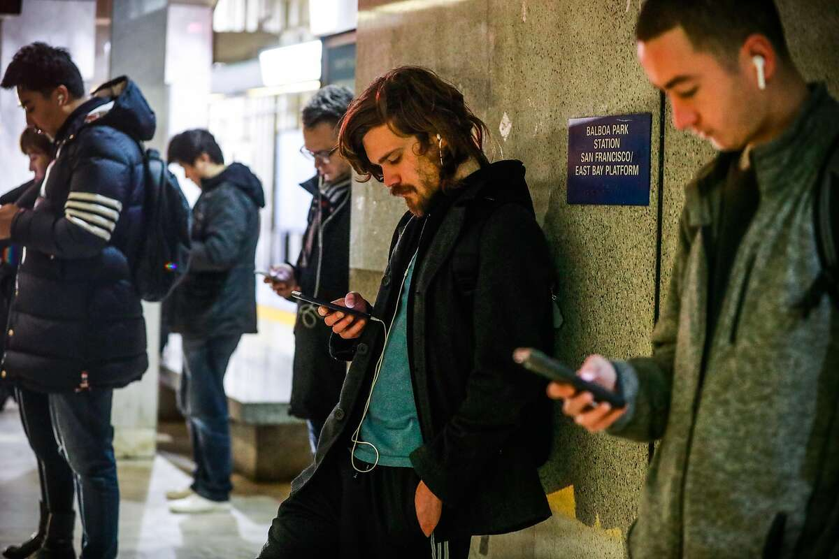 People look at their phones as they wait for the BART train at the Balboa Park station on Wednesday, Sept. 25, 2019 in San Francisco, California.The Balboa Park station experiences the most cell phone and laptop thefts in the city.