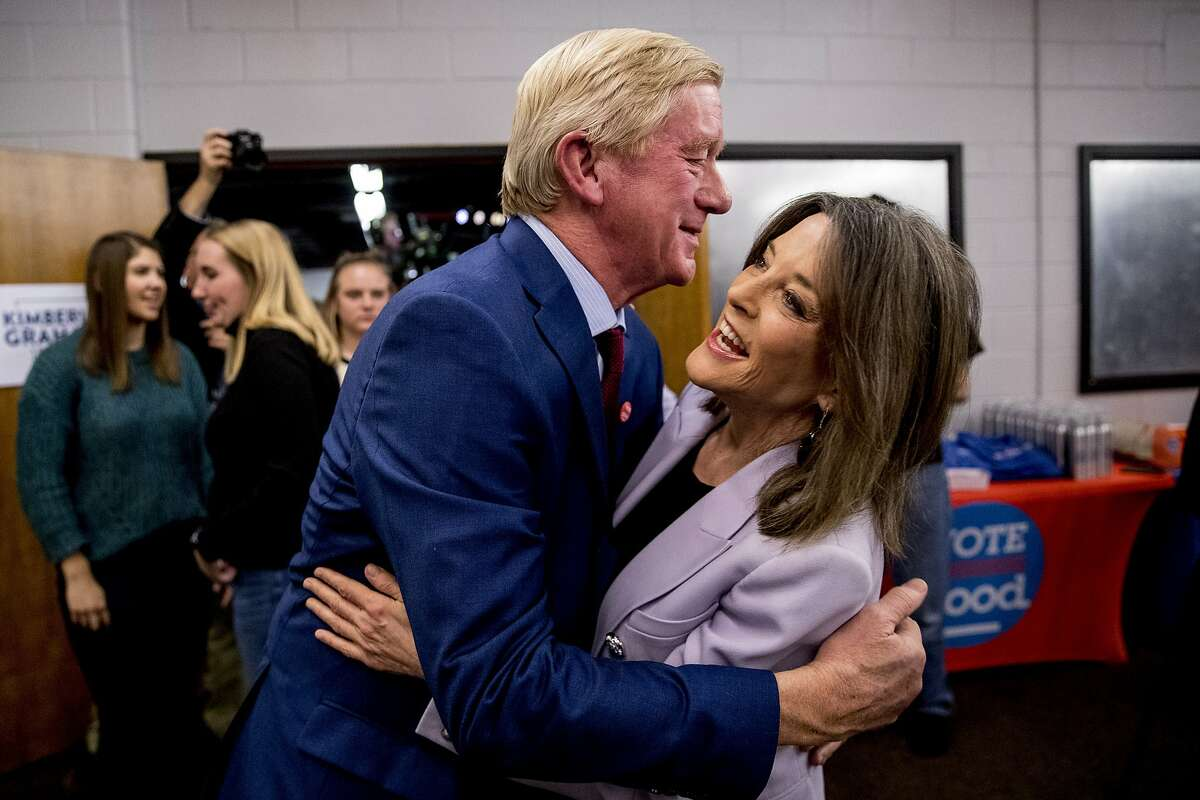 Republican presidential candidate former Massachusetts Gov. Bill Weld, left, and Democratic presidential candidate Marianne Williamson, right, greet each other at a Faith, Politics and the Common Good Forum at Franklin Jr. High School, Thursday, Jan. 9, 2020, in Des Moines, Iowa.