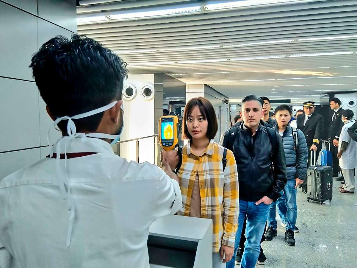 In this handout photograph taken and released by the Ministry of Civil Aviation (MoCA) on January 21, 2020, a man (L) uses a thermographic camera to screen the head of people at Netaji Subhash Chandra Bose International Airport in Kolkata, following the Ministry of Health and Family Welfare's advisory to screen passengers arriving in India from China and Hong Kong regarding the novel coronavirus (nCoV) issue. - Asian countries on January 21 ramped up measures to block the spread of a new virus as the death toll in China rose to six and the number of cases jumped to almost 300, raising concerns in the middle of a major holiday travel rush.