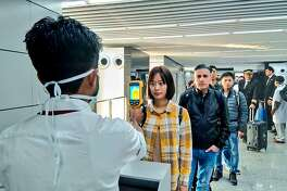 "In this handout photograph taken and released by the Ministry of Civil Aviation (MoCA) on January 21, 2020, a man (L) uses a thermographic camera to screen the head of people at Netaji Subhash Chandra Bose International Airport in Kolkata, following the Ministry of Health and Family Welfare's advisory to screen passengers arriving in India from China and Hong Kong regarding the novel coronavirus (nCoV) issue. - Asian countries on January 21 ramped up measures to block the spread of a new virus as the death toll in China rose to six and the number of cases jumped to almost 300, raising concerns in the middle of a major holiday travel rush. (Photo by Handout / Ministry of Civil Aviation (MoCA) / AFP) / RESTRICTED TO EDITORIAL USE - MANDATORY CREDIT ""AFP PHOTO / Ministry of Civil Aviation (MoCA)"" - NO MARKETING - NO ADVERTISING CAMPAIGNS - DISTRIBUTED AS A SERVICE TO CLIENTS (Photo by HANDOUT/Ministry of Civil Aviation (MoCA/AFP via Getty Images)"