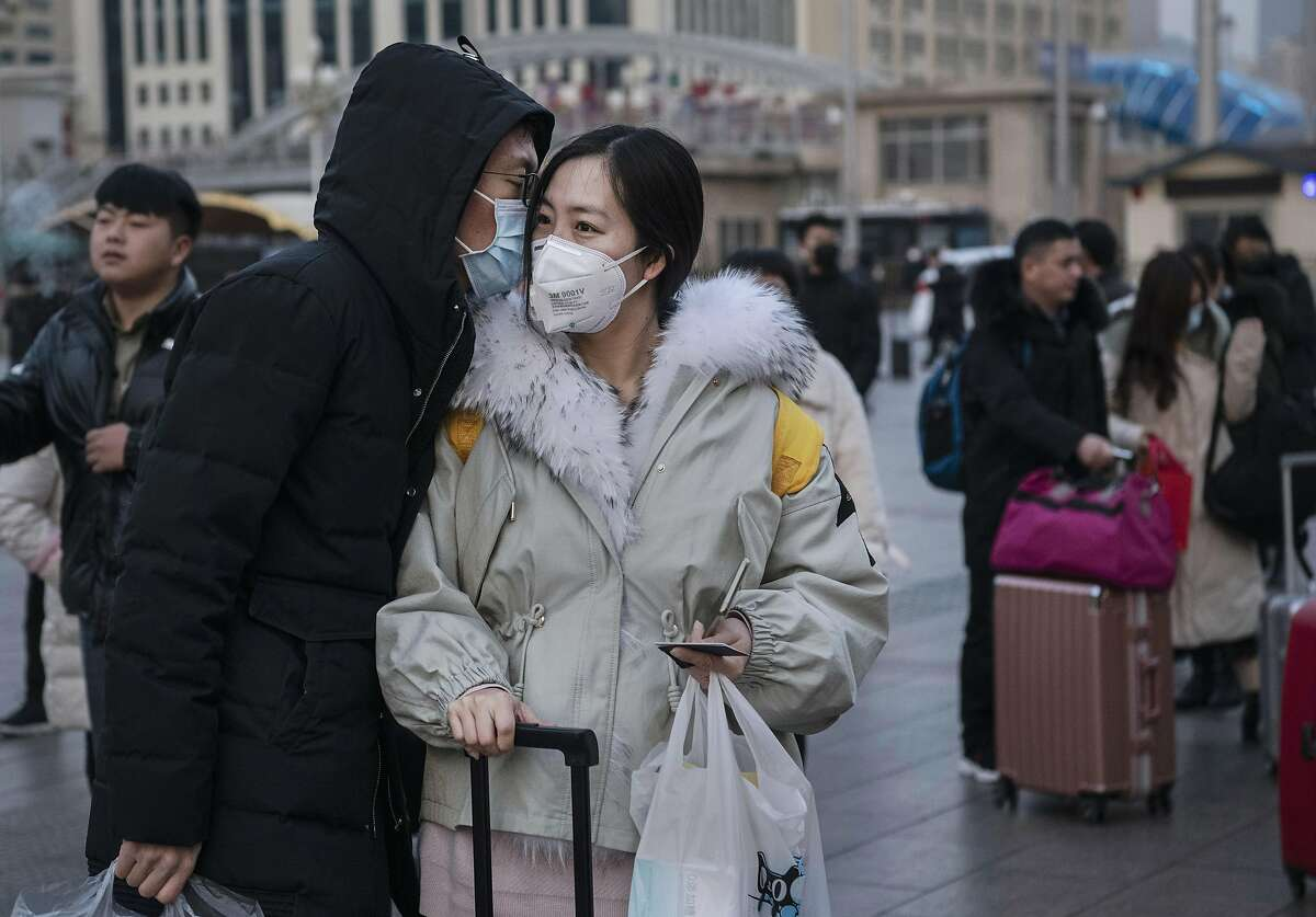BEIJING, CHINA - JANUARY 21: A Chinese man kisses his partner goodbye while both wear protective masks as she leaves to travel home at Beijing Railway station before the annual Spring Festival on January 21, 2020 in Beijing, China. The number of cases of a deadly new coronavirus rose to nearly 300 in mainland China Tuesday as health officials stepped up efforts to contain the spread of the pneumonia-like disease which medicals experts confirmed can be passed from human to human. The number of those who have died from the virus in China climbed to six on Tuesday and cases have been reported in other parts of Asia including in Thailand, Japan, Taiwan and South Korea. (Photo by Kevin Frayer/Getty Images)
