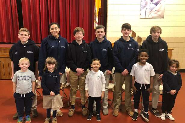 Holy Trinity Catholic Academy held its eighth grade pin ceremony Thursday, Jan. 16. Pictured are (back, left to right) Alex Balko, Tatiana Bell, Jacob Bisset, Matthew Conelius, Nicolas Coppola and Brady Grinvalsky with their kindergarten buddies (front, left to right) Jordan, Molly, Mason, Matai and Abby.