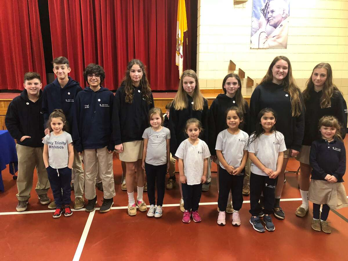 Holy Trinity Catholic Academy held its eighth grade pin ceremony Thursday, Jan. 16. Pictured are (back, left to right) Antonio Salerno, Aiden Tomlinson, Kushal Singh, Mia Koletsos, Victoria Pecirep, Gabby MacDaniel, Erin Wilson and Francesca Xhokola with their kindergarten buddies (front, left to right Sophia, Mia, Lydia, Nicole, Kendra and Molly.