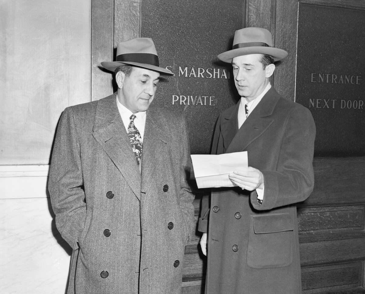 Tony Accardo, (left), the reputed kingpin in a nationwide crime syndicate, reads the subpoena from the Senate Crime Investigating Committee in 1950 that his attorney George Callaghanholds.