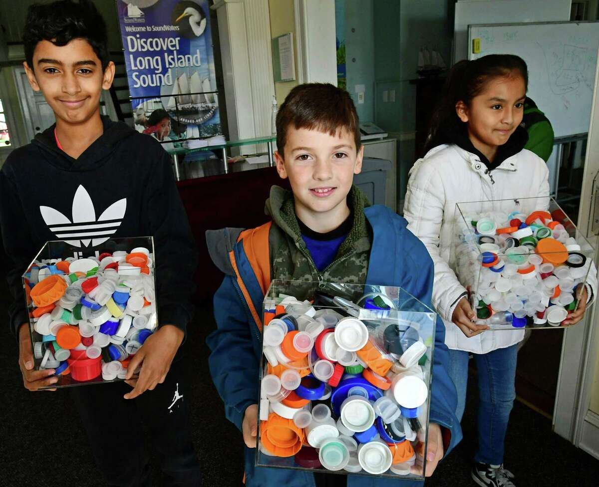Sixth graders from Dolan Middle School Jayden Howard, Tyler O'Grady and Litzi Najera display some of the bottle caps they collected learn about how plastics enter the ecosystem in conjunction with the The One Million Bottle Cap Challenge Friday, November 1, 2019, at the Soundwaters headquarters at Cove Island Park in Stamford, Conn. SoundWaters has launched the initiative with Stamford Public Schools to have students remove one million bottle caps before they reach the Sound during the school year.