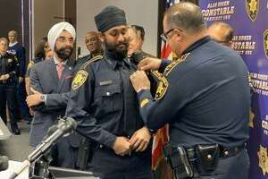 Harris County Constable Deputy Amrit Singh (left) is pinned by Precinct 1 Constable Alan Rosen (right) after being sworn in on Tuesday, Jan. 21. Singh is Harris County's first Sikh deputy constable.