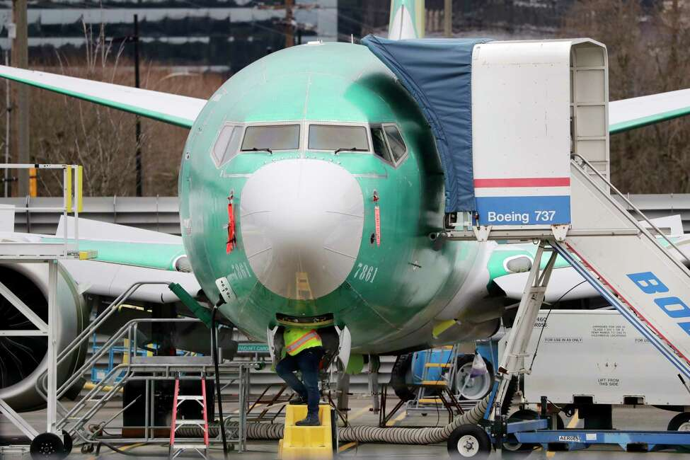 FILE - In this Dec. 16, 2019, file photo a worker looks up underneath a Boeing 737 MAX jet in Renton, Wash. Boeing doesn't expect federal regulators to approve its changes to the grounded 737 Max until this summer, according to two people familiar with the matter. (AP Photo/Elaine Thompson, File)