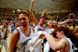 UConn's Rebecca Lobo, left, cheers as she runs off the floor after No. 2 Connecticut defeated top-ranked Tennessee, 77-66, in Storrs, Conn. on Monday, Jan. 16, 1995. Behind Lobo is teammate Kara Wolters, and at right is Jennifer Rizzotti.