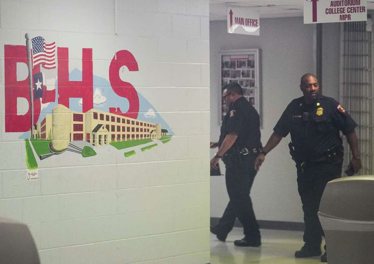 Police officers walk back into Bellaire High School after escorting Houston ISD Interim Superintendent Grenita Lathan outside to speak to the media on Jan. 14 about the on-campus shooting death of 19-year-old Cesar Cortes.