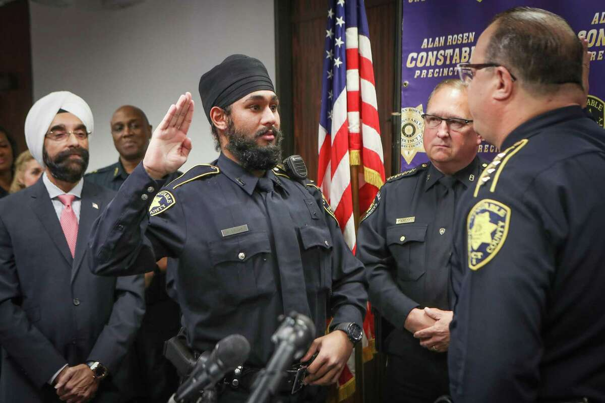 """Deputy Amrit Singh, second from right, talks to the media after being sworn-in by Constable Alan Rosen Tuesday, Jan. 21, 2020, in Houston. Singh is the first Sikh Deputy Constable in Harris County history. His swearing-in coincides with the adoption by nearly all Harris County Constables of a religious """"Articles of Faith"""" policy which allows all those who serve to wear articles of faith while discharging their duties in uniform."""