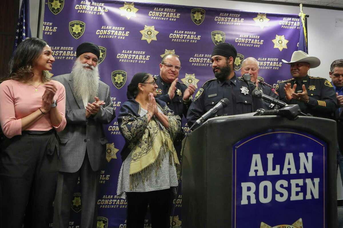 "Deputy Amrit Singh receives applause from his sister Satnam Kaur (l-r), father Satnam Singh, mother Sukie Kaur, Constable Alan Rosen and other Constables after being sworn in Tuesday, Jan. 21, 2020, in Houston. Singh is the first Sikh Deputy Constable in Harris County history. His swearing-in coincides with the adoption by nearly all Harris County Constables of a religious ""Articles of Faith"" policy which allows all those who serve to wear articles of faith while discharging their duties in uniform."