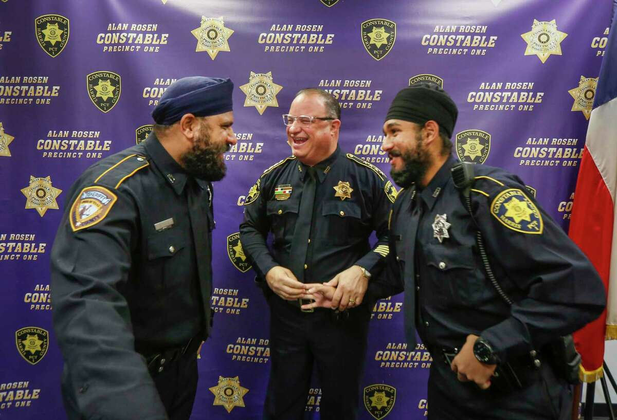 """Harris County Sheriff Deputy Navdeep Nijjar, Constable Alan Rosen and Deputy Amrit Singh share a light moment after Singh was sworn-in Tuesday, Jan. 21, 2020, in Houston. Singh is the first Sikh Deputy Constable in Harris County history. His swearing-in coincides with the adoption by nearly all Harris County Constables of a religious """"Articles of Faith"""" policy which allows all those who serve to wear articles of faith while discharging their duties in uniform."""