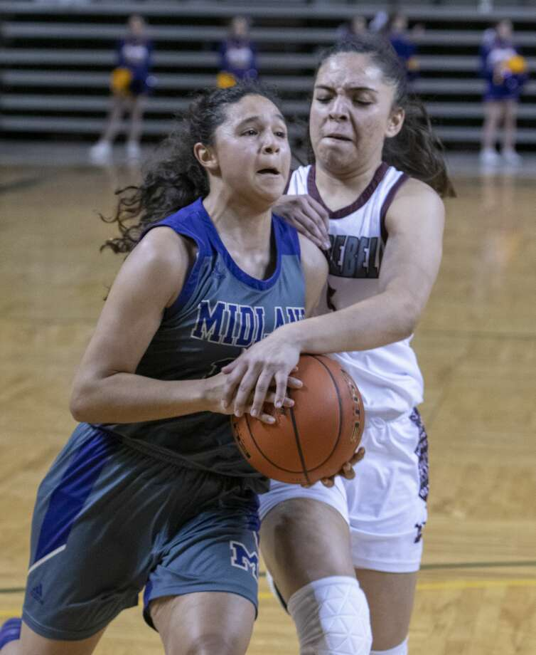 Midland High's Noemi Arciga is fouled by Lee High's Salma Trejo as she drives to the basket 01/21/20 at the Chaparral Center. Tim Fischer/Reporter-Telegram Photo: Tim Fischer/Midland Reporter-Telegram