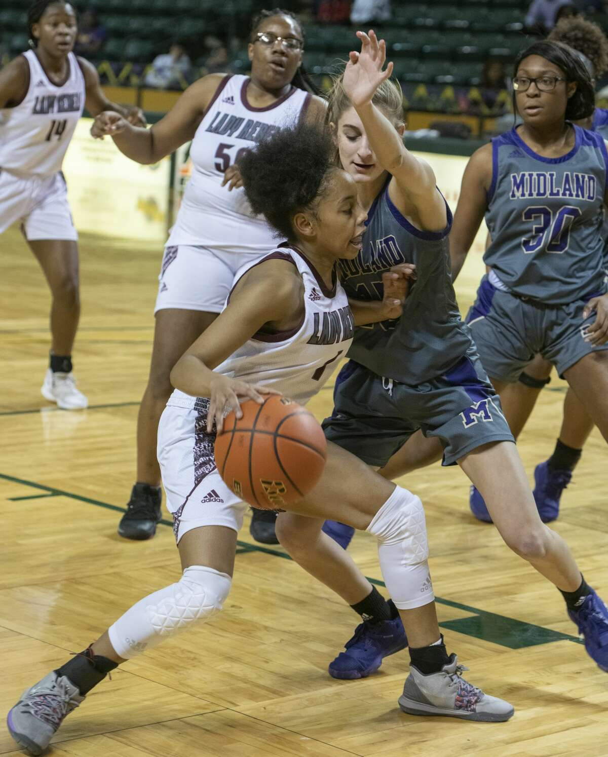 Lee High's Myleah Young tries to drive to the basket as Midland High's Sam Braudaway defends 01/21/20 at the Chaparral Center. Tim Fischer/Reporter-Telegram