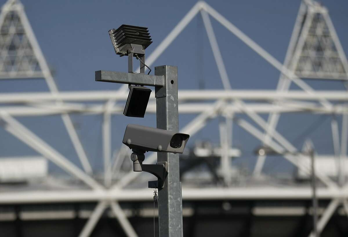 FILE - In this file photo dated Wednesday, March 28, 2012, a security cctv camera is seen by the Olympic Stadium at the Olympic Park in London. The South Wales police deployed facial recognition surveillance equipment on Sunday Jan. 12, 2020, in a test to monitor crowds arriving for a weekend soccer match in real-time, that is prompting public debate about possible aggressive uses of facial recognition in Western democracies, raising questions about human rights and how the technology may enter people's daily lives in the future. (AP Photo/Sang Tan, FILE)