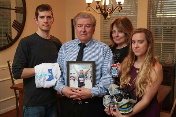 Harry Vroulis' family, nephew John Paul Vroulis (l-r), brother George and his wife Diane, and niece Christina Vroulis hold some of Harry's running gear and a photo of him Tuesday, Jan. 21, 2020, in Houston. The 74-year-old native of Athens, Greece, died Sunday Chevron Marathon Houston.