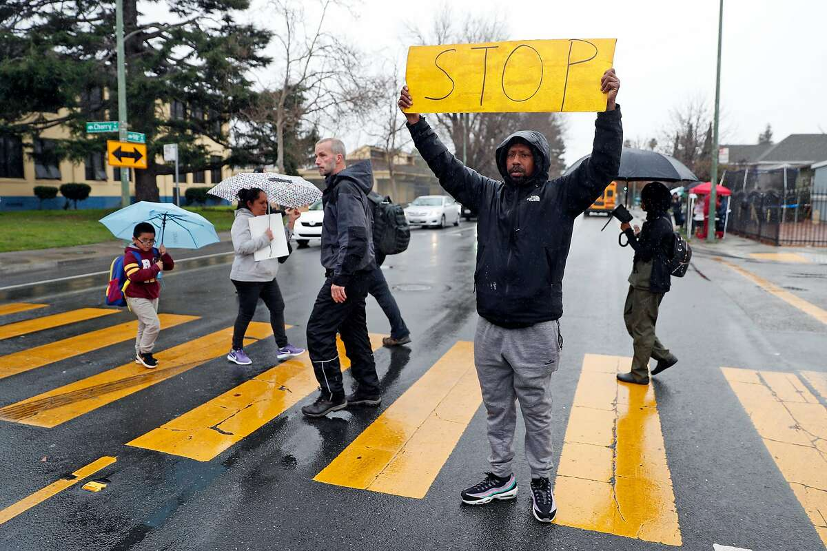 Daryle Allums, brother of Miesha Singleton, performs crossing guard duties, at the scene of the death by hit and run driver of Singleton in front of Elmhurst United Middle School in Oakland, Calif., on Tuesday, January 21, 2020.