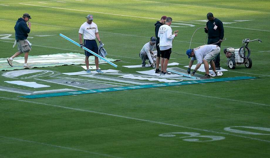 Workers paint the field at Hard Rock Stadium Stadium in Miami Gardens, Fla., on Tuesday, Jan. 21, 2020, in anticipation of Super Bowl LIV, featuring the Kansas City Chiefs against the San Francisco 49ers on February 2, 2020. (Mike Stocker/Sun Sentinel/TNS) Photo: Mike Stocker / TNS
