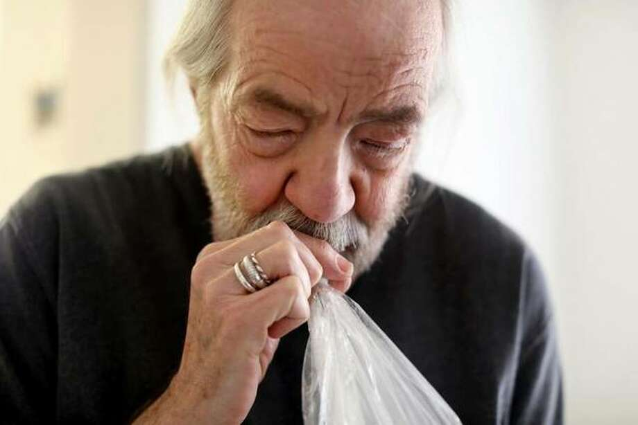 In this March 20, 2019 photo Gary Storck inhales marijuana from a vaporizer in his apartment on March 20, 2019 in Madison, Wisc., to relieve the symptoms of glaucoma. Storck is a leading advocate of legalizing marijuana for medical use in Wisconsin. He co-founded the group, Is My Medicine Legal Yet?, and he writes the Cannabadger blog, which tracks proposals to legalize marijuana in Wisconsin. (Coburn Dukehart/Wisconsin Center for Investigative Journalism via AP)
