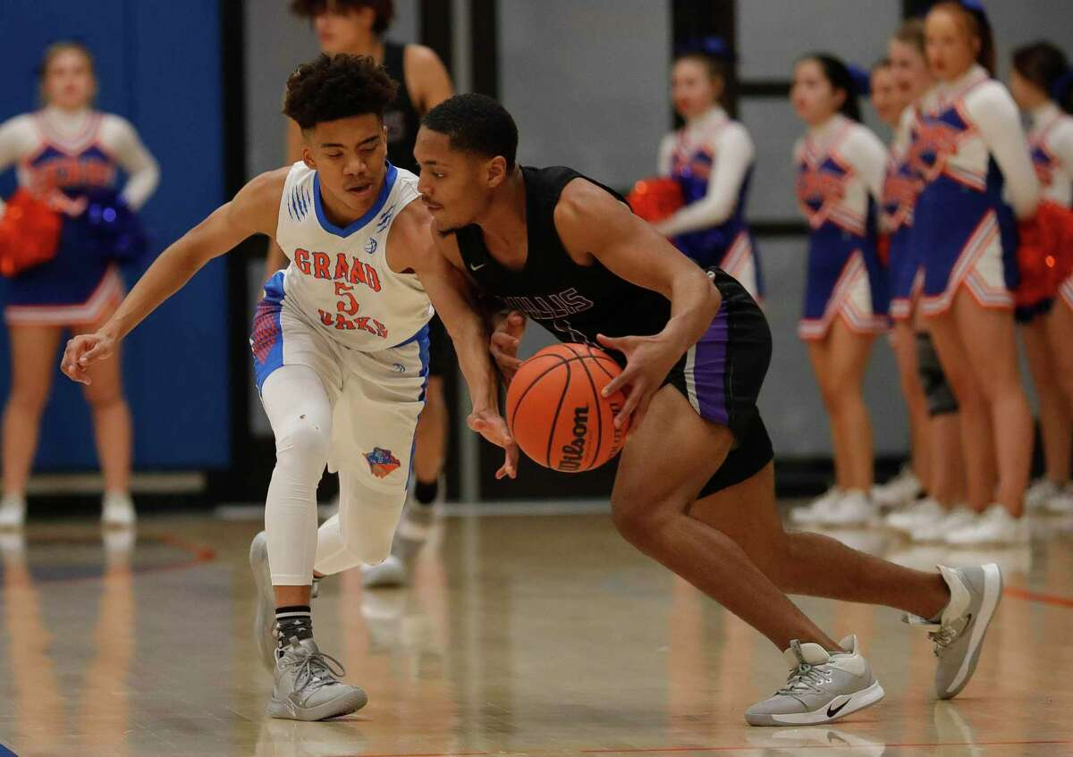 Grand Oaks guard Chamberlain Newman (5) knocks the ball away from Willis guard Charles Kibble (1) during the first quarter of a District 20-5A high school basketball game at Grand Oaks High School, Tuesday, Jan. 21, 2020, in Spring.
