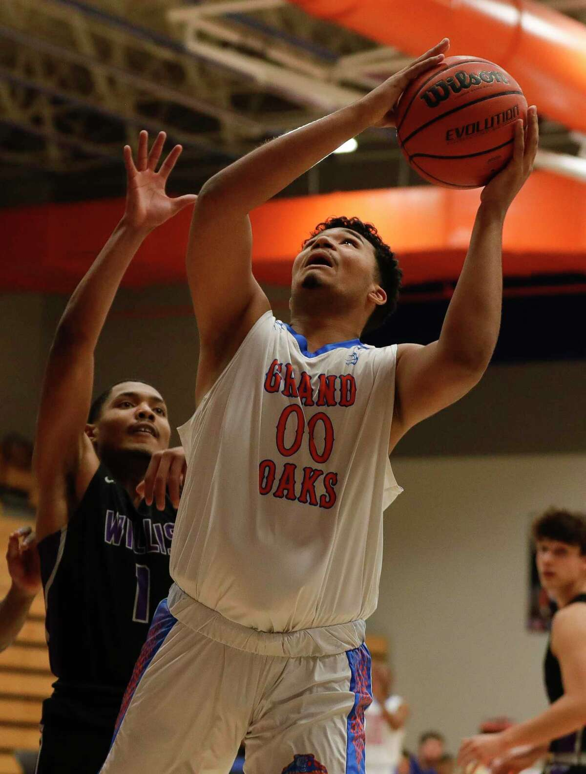 Grand Oaks center CJ Jones (00) shoots as Willis guard Charles Kibble (1) defends during the first quarter of a District 20-5A high school basketball game at Grand Oaks High School, Tuesday, Jan. 21, 2020, in Spring.