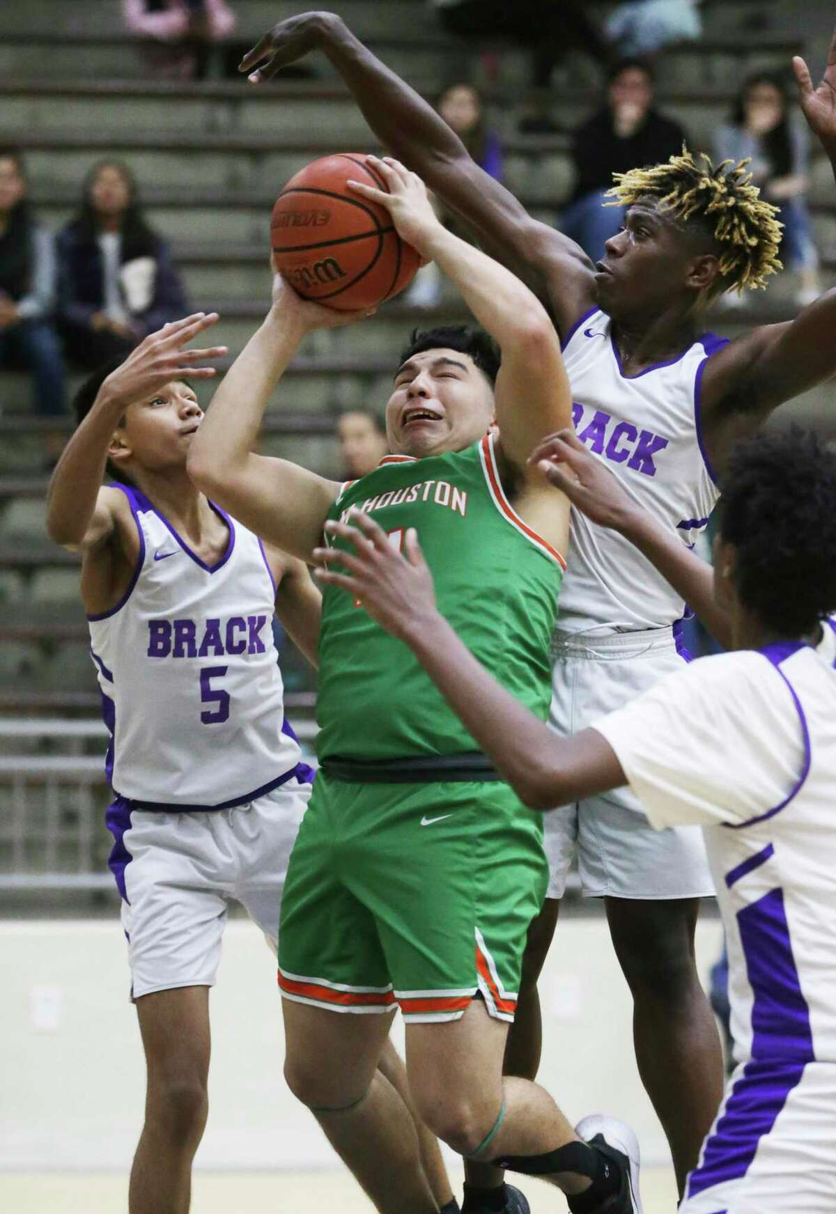 Jesus Alonzo gets stopped under the basket by Eagle defenders Isaiah Perales, 5, and Kalvin Nance as Sam Houston plays Brackenridge in boys basketball at the Alamo Convocation Center on Jan.21, 2020.