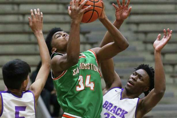 Hurricane forward Darrius Govan pulls down a rebound between Isaiah Perales , 5, and Korian Bragg as Sam Houston plays Brackenridge in boys basketball at the Alamo Convocation Center on Jan.21, 2020.