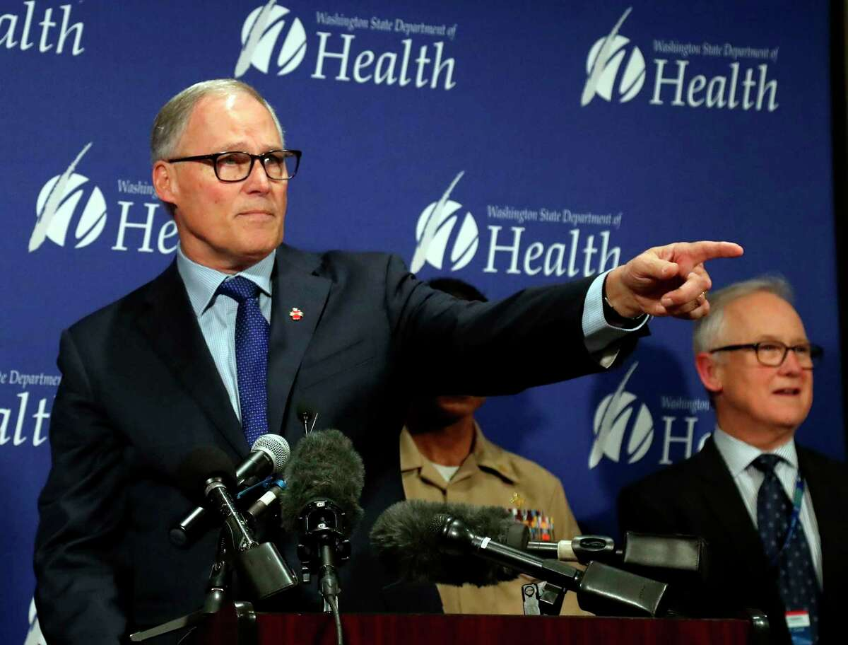 Gov. Jay Inslee, left, and other health professionals speak during a press conference at Public Health Laboratories, Tuesday, Jan. 21, 2020, in Shoreline, Wash. Looking on at far right is Dr. Jay Cook, Providence Regional Medical Center Everett. The U.S. on Tuesday reported its first case of a new virus circulating in China, saying a Washington state resident who returned last week from the outbreak's epicenter was hospitalized near Seattle. (Greg Gilbert/The Seattle Times via AP)
