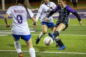 Willis defender Vivienne McConnell-Tatsch (24) passes the ball while under pressure from Grand Oaks defender Lauren Moylan (23) and Grand Oaks forward Rylee Friedrich (9) during a District 20-5A high school soccer match at Berton A. Yates Stadium, Tuesday, Jan. 21, 2020, in Willis.
