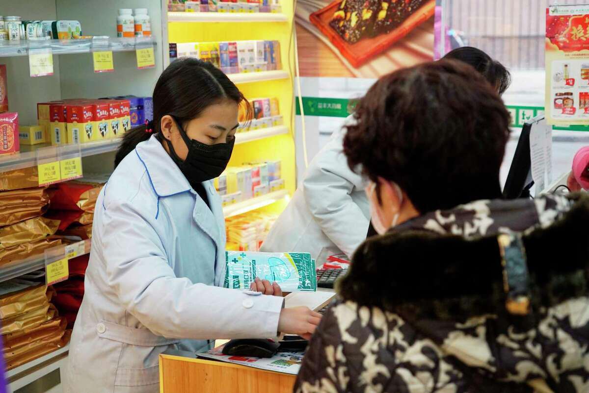 Staff sell masks at a Yifeng Pharmacy in Wuhan, Chin, Wednesday, Jan. 22, 2020. Pharmacies in Wuhan are restricting customers to buying one mask at a time amid high demand and worries over an outbreak of a new coronavirus. The number of cases of the new virus has risen over 400 in China and the death toll to 9, Chinese health authorities said Wednesday.