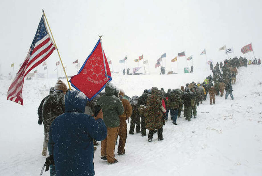 Hundreds of veterans who vowed to defend the Standing Rock protest camp march through a 2015 winter blizzard to the scene of clashes with state police and the National Guard just outside the Lakota Sioux reservation of Standing Rock, North Dakota. More than 200 tribes, joined by environmental activists and others, camped and demonstrated against the Dakota Access Pipeline. Photo: Andrew Lichtenstein | Corbis (Getty Images)