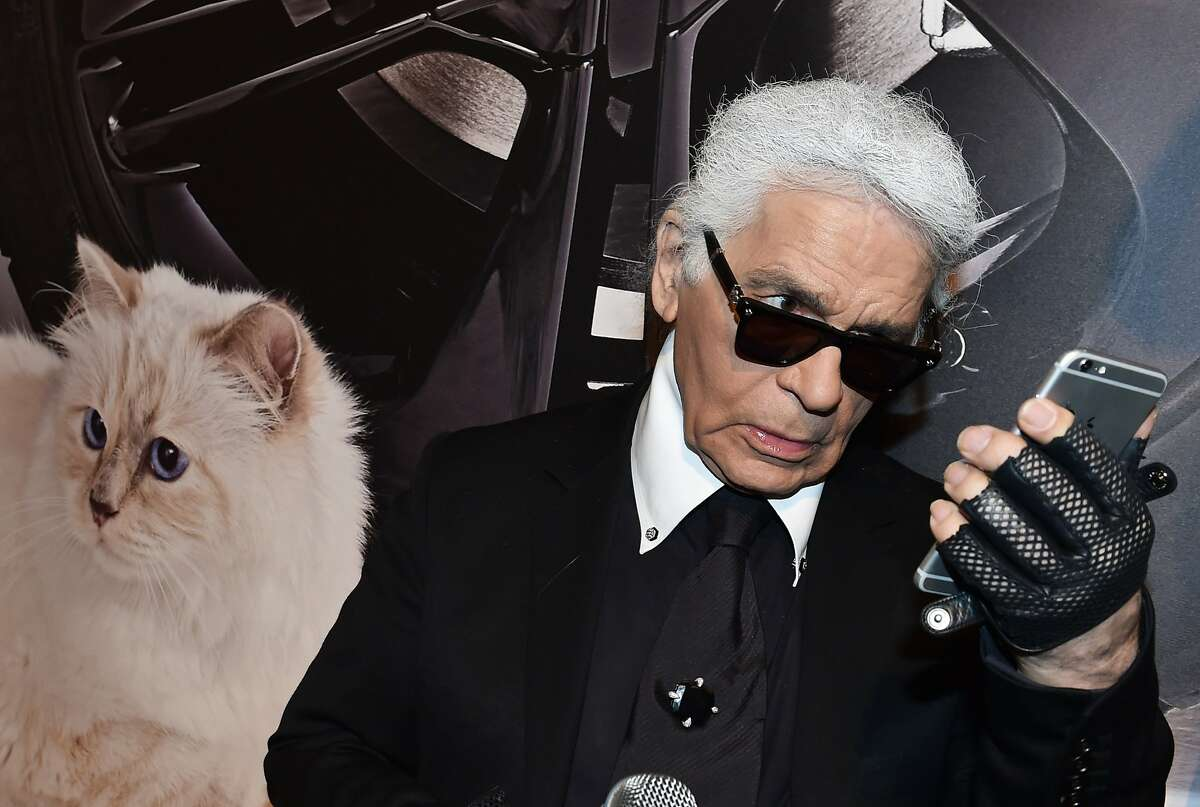 German fashion designer, artist, and photographer Karl Lagerfeld poses next to a photo of his cat