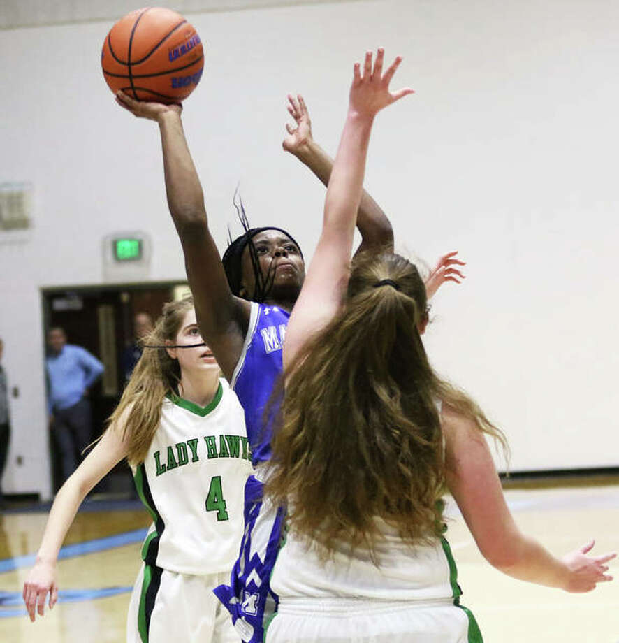Marquette Catholic's Adrenna Snipes (middle) pulls up to shoot over Carrollton's Ava Uhles in a Dec. 27 game at the Jersey Holiday Tourney. On Tuesday night in Alton, Snipes scored 33 points to surpass 1,000 career points in her sophomore season with the Explorers. Photo: Greg Shashack / The Telegraph