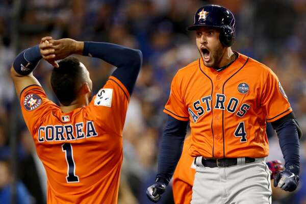 George Springer #4 of the Houston Astros celebrates with Carlos Correa #1 after hitting a two-run home run during the second inning against the Los Angeles Dodgers in game seven of the 2017 World Series at Dodger Stadium on November 1, 2017 in Los Angeles, California.
