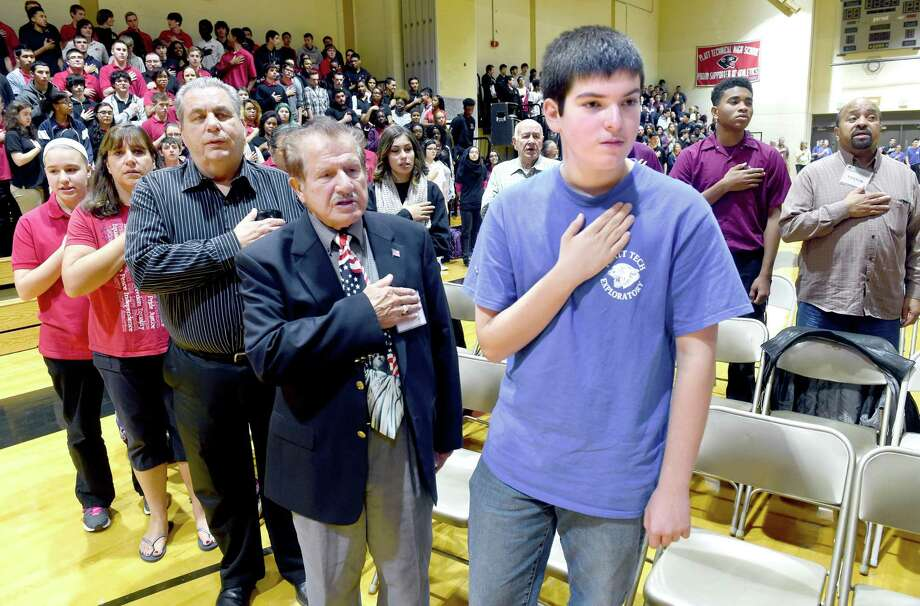 Korean War Army veteran Joseph DiMenna (center) of Trumbull and his grandson, Anthony DeMenna (right, 15, of Shelton stand at attention during the Pledge of Allegiance at the Platt Technical High School's Veteran's Day Celebration in Milford on 11/6/2015. Photo: Arnold Gold / Hearst Connecticut Media