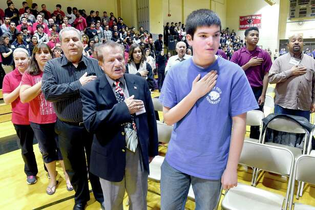 Korean War Army veteran Joseph DiMenna (center) of Trumbull and his grandson, Anthony DeMenna (right, 15, of Shelton stand at attention during the Pledge of Allegiance at the Platt Technical High School's Veteran's Day Celebration in Milford on 11/6/2015.