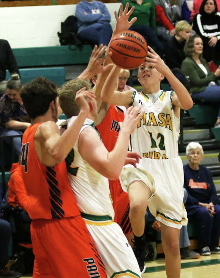 Southwestern's Keegan Rowell (right) puts up a shot in traffic in a SCC game vs. Pana on Jan. 10 in Piasa. On Tuesday night at the Macoupin County Tourney in Staunton, Rowell had five 3-pointers and 19 points to lead the Birds to an overtime victory over Gillespie. Photo: Greg Shashack / The Telegraph